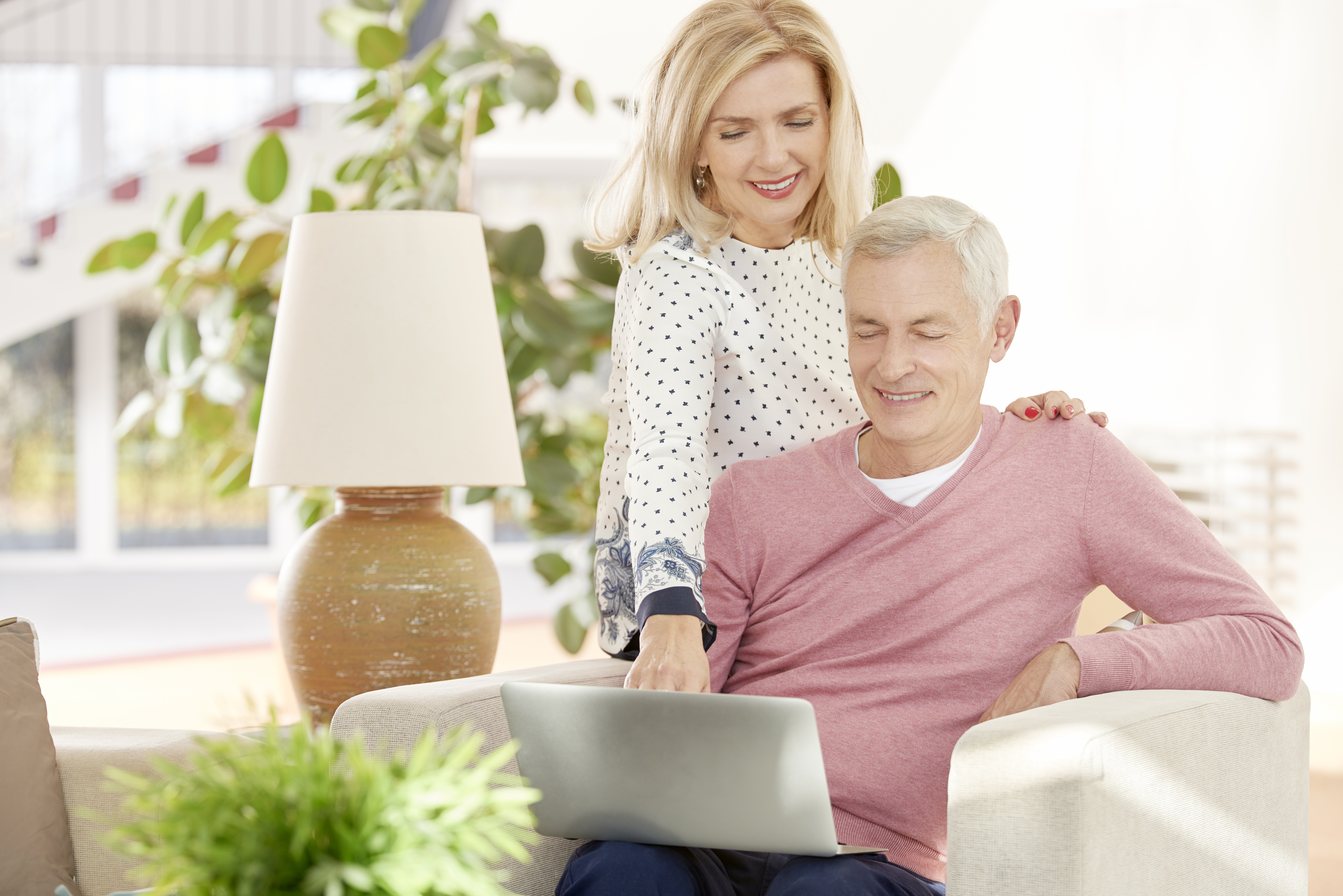 Mature couple planning donations on laptop